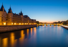 France, Ile-de-France, Paris, Conciergerie And Seine Canal At Dusk With Pont Neuf In Background