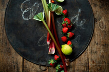 Fresh Rhubarb, Strawberries, Lemon And Lime On Rustic Baking Sheet