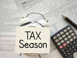 Tax-filling concept - Tax season text on white surface. Top view vintage background. Stock photo.