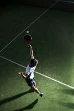 Male Athlete Servicing Ball While Playing Padel Tennis In Sports Court At Night