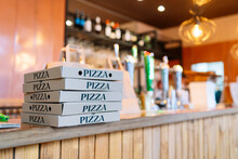 Stack Of Pizza Boxes Kept On Counter At Restaurant