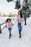 Smiling mother and daughter holding hands while walking in park