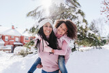 Mother looking away while giving piggyback ride to daughter on snow covered land