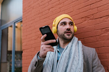 Man With Headphones Using Mobile Phone While Standing Against Brick Wall
