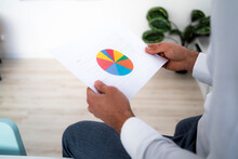 Male Entrepreneur Holding Pie Chart While Working In Office