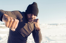 Male Athlete Wearing Knit Hat Showing Fist While Practicing Boxing Outdoors