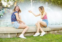 Cheerful Female Friends Sitting On Retaining Wall By Fountain In Public Park