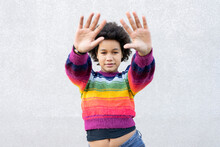 Girl With Hand Raised Standing Against Gray Wall