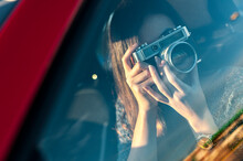 Young Woman Photographing From Vintage Camera Through Car Glass Window