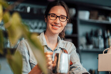 Smiling Female Manager With Coffee Pot In Cafe