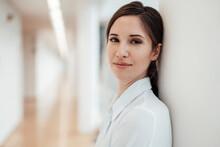 Smiling Female Entrepreneur Against Wall In Office