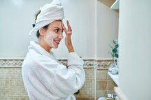 Smiling Woman Applying Face Cream While Standing In Bathroom