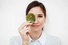 Businesswoman Holding Leaf On Her Eye Against White Background In Studio