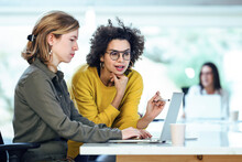 Female Colleagues Planning Strategy While Discussing Over Laptop At Desk In Office