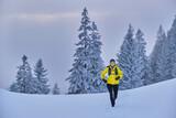 Female explorer running in snow over mountain at Heimgarten at Bavaria, Germany