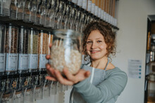 Smiling Female Saleswoman Showing Glass Jar With Food While Standing In Zero Waste Store