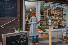 Young Female Entrepreneur In Mask Holding Digital Tablet While Standing Against Store