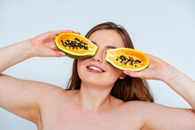 Close-up Of Topless Young Woman Holding Papaya Slices On Eyes Against White Background