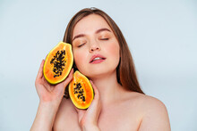 Close-up Of Topless Woman With Eyes Closed Holding Papaya Slices Against White Background