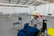 Senior Women Wearing Protective Face Mask And Warm Clothing Sitting On Wheelchair At Vaccination Center