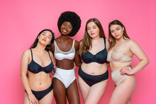 Multi-ethnic Group Of Female Models In Lingerie Standing With Arms Around Waist Against Pink Background