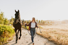 Women Walking With Horses On Pathway Amidst Field Against Sky