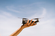 Hand Of Mature Woman Holding Drone Against Sky During Sunny Day
