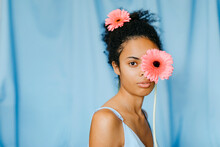 Young Woman With Gerbera Daisy In Front Of Eye Against Blue Curtain