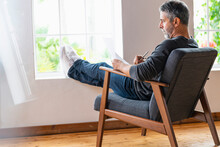 Businessman Writing In Paper While Sitting With Leg Crossed On Armchair At Home