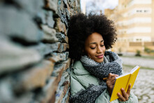 Smiling Afro Woman Writing In Book While Leaning On Stone Wall During Winter