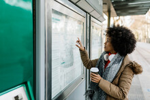 Afro Woman With Disposable Coffee Cup And Headphones Checking Map At Bus Stop