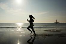 Sportswoman Running Along Beach