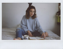 Young Woman Reading A Book On Her Bedroom