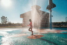 Cute Adorable Caucasian Funny Girl Playing On Splash Pad Playground On Summer Day. Seasonal Water Sport Recreational Activity For Kids Outdoors.