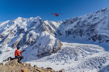 A Beautiful Landscape With Mountains, A Huge Blue Glacier And A Middle-aged Mountaineer Sitting With A Walkie-talkie In His Hands Calls The Rescue Service Waiting For An Ambulance Helicopter