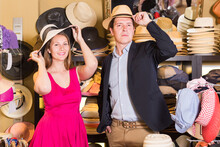 Attractive Young Female And Man Choosing Hats From The Assortment In The Store