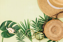Tropical Palm Leaves, Straw Hat On Green Background. Trendy Tropical Pattern. Fashion Clothing And Accessories. Flat Lay. Summer, Vacation, Holidays Concept.