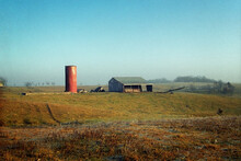 A Barn And Red Brick Grain Silo On A Hillside On A Misty Morning. Near Pure Air, Missouri, 1994.