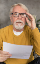 Portrait Of An Elderly Man With Gray Hair And A Beard Looking At Camera Holding Credit Bill Or Utility Bill