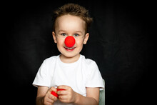 Boy With A Clown Red Nose And Red Noses In His Hands. Red Nose Day.