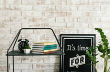 Stack Of Books And Alarm Clock On Table Against Brick Wall