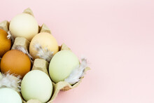 Close Up View Of Raw Multicolored Chicken Eggs In Ovum On Pink Background