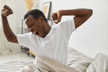 Lazy Carefree Young African Man Waking Up Late After Party. Dark Skinned Guy Sitting On Bed With Raised Hands, Eyes Closed And Mouth Wide Opened, Yawning With Enjoyment Early In The Morning