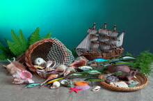 Marine Still Life. Model Of A Sailing Ship, Wooden Fish, A Piece Of Net, Shells, Amphora, Coins On The Seabed.