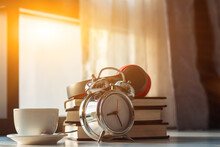 An Alarm Clock Placed Beside A Textbook On A Desk By A Window In The Bedroom In The Morning Was Prepared For Reading After The Clock Woke Up To Learn To Understand Before Going To The Exam.