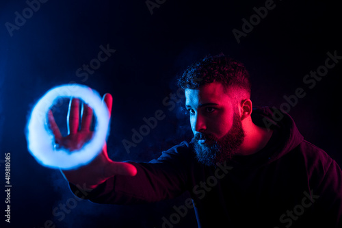 Slika na platnu Young bearded arab man smoking vape and making smoke rings in dark studio with colored lights