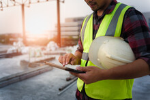 Engineering Consulting People On Construction Site Holding Tablet In His Hand. Management In Business Workflow And Building Inspector With BIM Technology In Construction Project.