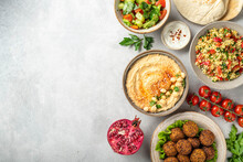 Middle Eastern Or Arabic Cuisines, Falafel, Hummus, Tabouleh, Pita And Vegetables On A Concrete Background, View From Above, Copy Space