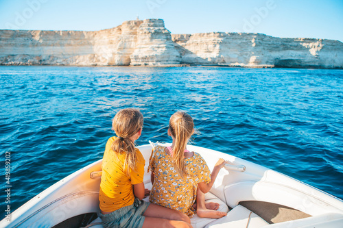 Canvas Little girls sailing on boat in clear open sea