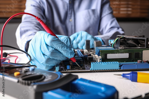 Technician repairing electronic circuit board at table, closeup Fototapet